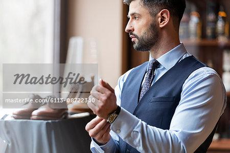 Businessman looking through window in menswear shop