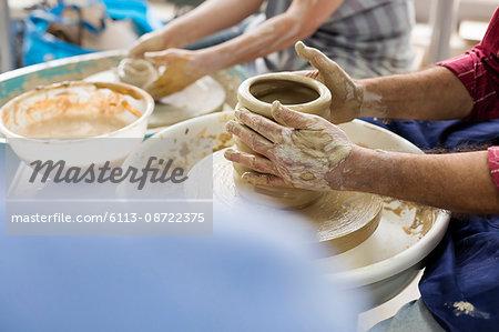 Senior man using pottery wheel in studio