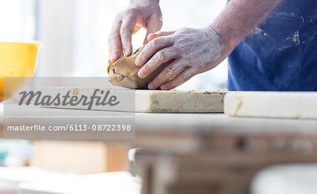 Senior man molding clay in pottery studio