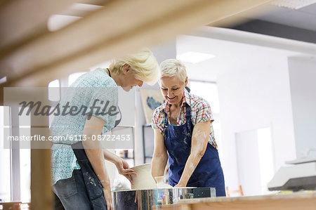 Women placing pottery in kiln in studio
