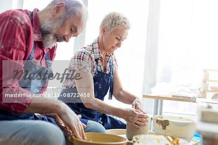 Senior couple using pottery wheels in studio