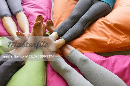 Women's bare feet connection on restorative yoga cushions