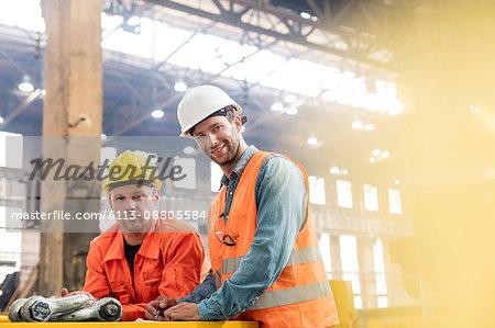 Portrait confident steel factory workers in factory
