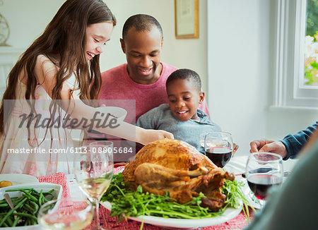 Multi-ethnic family enjoying Christmas turkey dinner at table