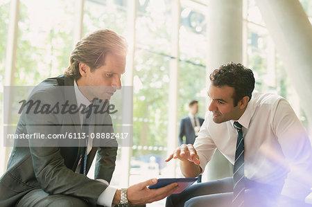 Businessmen meeting using digital tablet in office lobby
