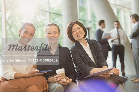 Portrait smiling businesswomen meeting in office lobby