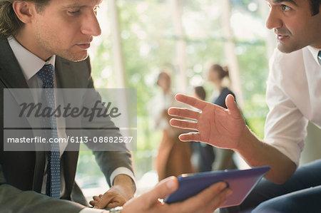Businessmen with digital tablet talking