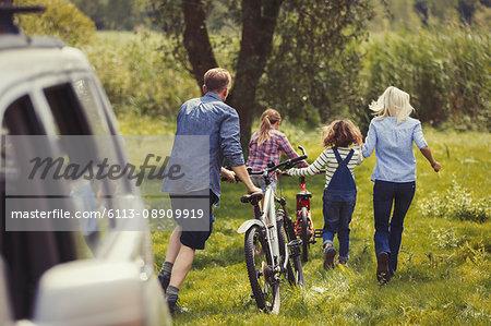 Family walking mountain bikes away from car