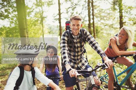 Smiling family mountain biking in woods