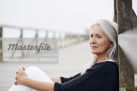 Pensive senior woman relaxing on beach boardwalk