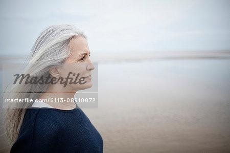 Pensive senior woman looking away on winter beach