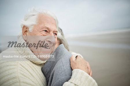 Affectionate senior couple hugging on winter beach