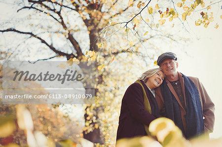 Affectionate senior couple hugging in sunny autumn park