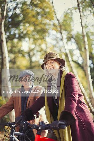 Portrait smiling senior couple bike riding in autumn park