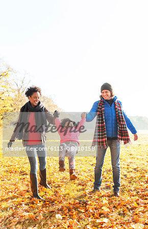 Parents swinging daughter in sunny autumn park