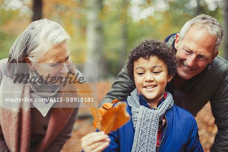 Grandparents and grandson holding autumn leaf