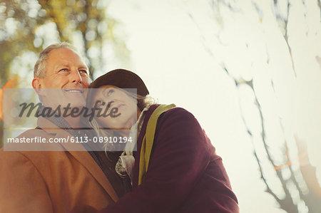 Affectionate, serene senior couple in autumn park