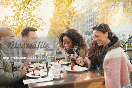 Friends eating cheesecake dessert at autumn sidewalk cafe