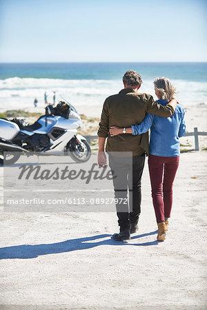 Affectionate senior couple walking on sunny beach toward motorcycle