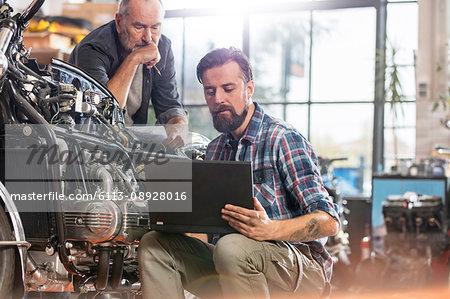 Male motorcycle mechanics using laptop in workshop