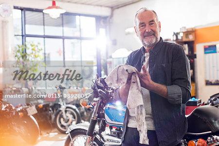 Portrait smiling senior male motorcycle mechanic wiping hands on rag in workshop