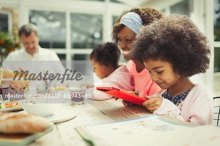 Girl using digital tablet at breakfast table