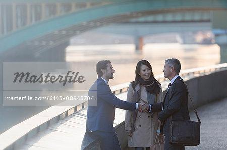 Businessmen handshaking at urban waterfront