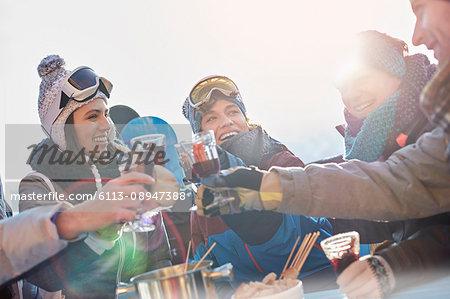 Skier friends toasting cocktail glasses apres-ski