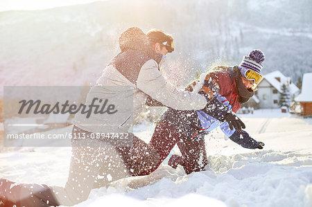 Playful couple enjoying snowball fight in snowy field