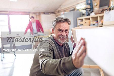 Smiling male carpenter examining wood boat in workshop