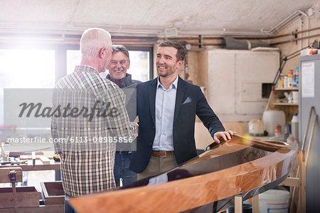 Male carpenters handshaking with satisfied customer next to wood kayak in workshop