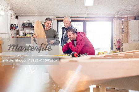 Male carpenters using laptop near wood boat in workshop