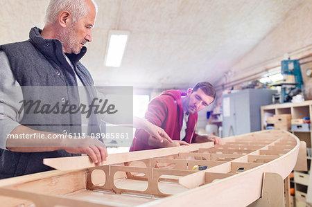 Male carpenters assembling wood boat in workshop