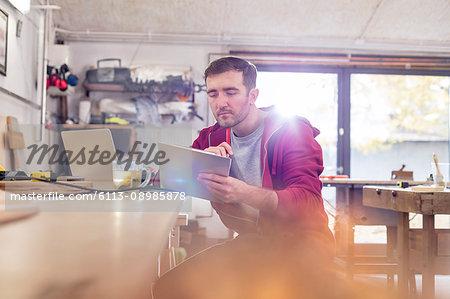 Male carpenter using digital tablet, drinking tea at workbench in workshop