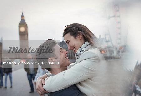 Romantic, affectionate couple tourists hugging near Big Ben, London, UK
