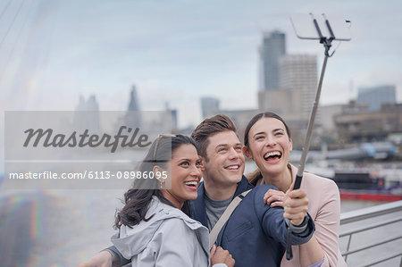 Enthusiastic, smiling friend tourists taking selfie with selfie stick on urban bridge, London, UK