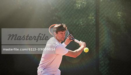 Young man playing tennis, swinging tennis racket