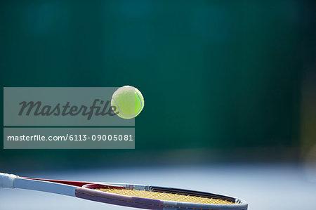 Tennis ball bouncing on tennis racket