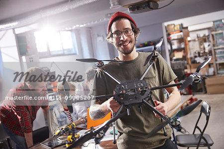 Portrait smiling male designer holding drone in workshop