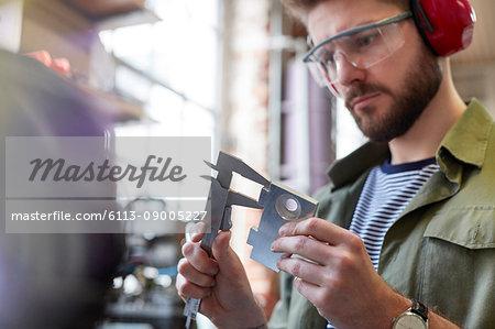Male designer using calipers in workshop