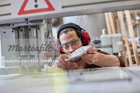 Male designer wearing ear protectors, examining prototype in workshop