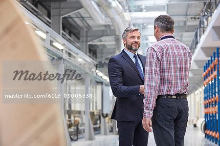Business owner and supervisor handshaking in fiber optics factory