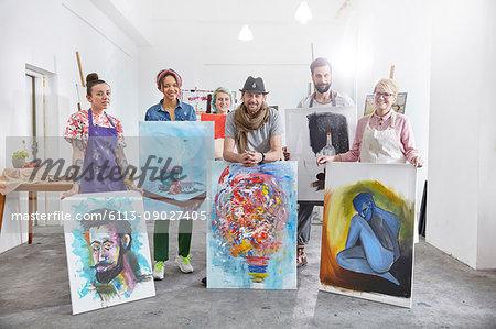 Portrait confident artists showing paintings in art class studio