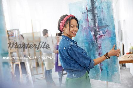Portrait smiling female artist lifting painting in art class studio