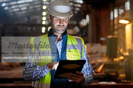 Male engineer working at glowing digital tablet in dark factory