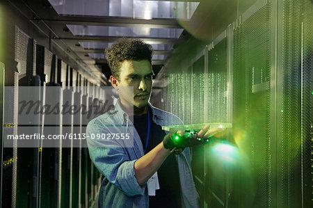 Male IT technician holding glowing futuristic digital tablet in server room