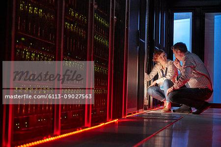 IT technicians talking at glowing panel in dark server room