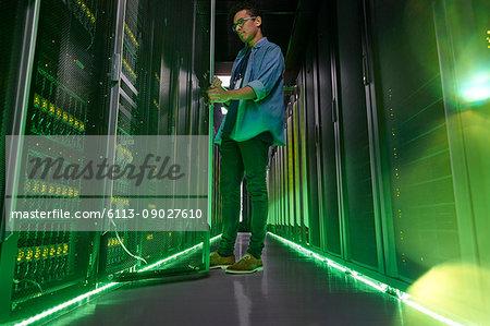 Male IT technician working in dark server room with glowing green panels