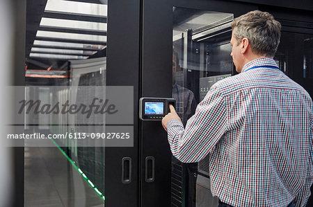 Male IT technician inputting security code at server room access door