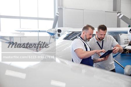 Male mechanic engineers using digital tablet near airplane in hangar